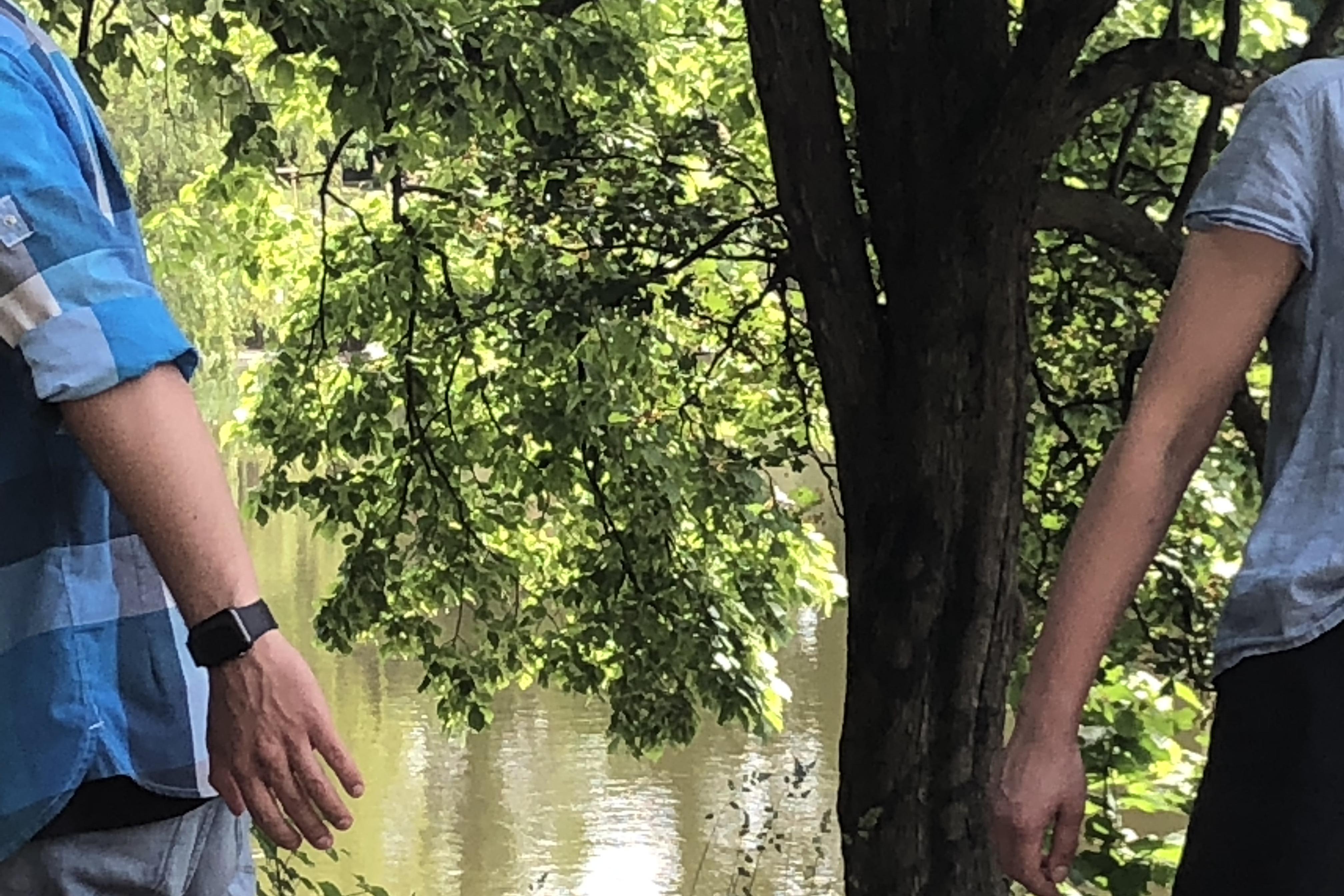 Zwei Personen draußen vor grünem Baum und See, nur zur Hälfte zu sehen, bewegen sich aus dem Bild.