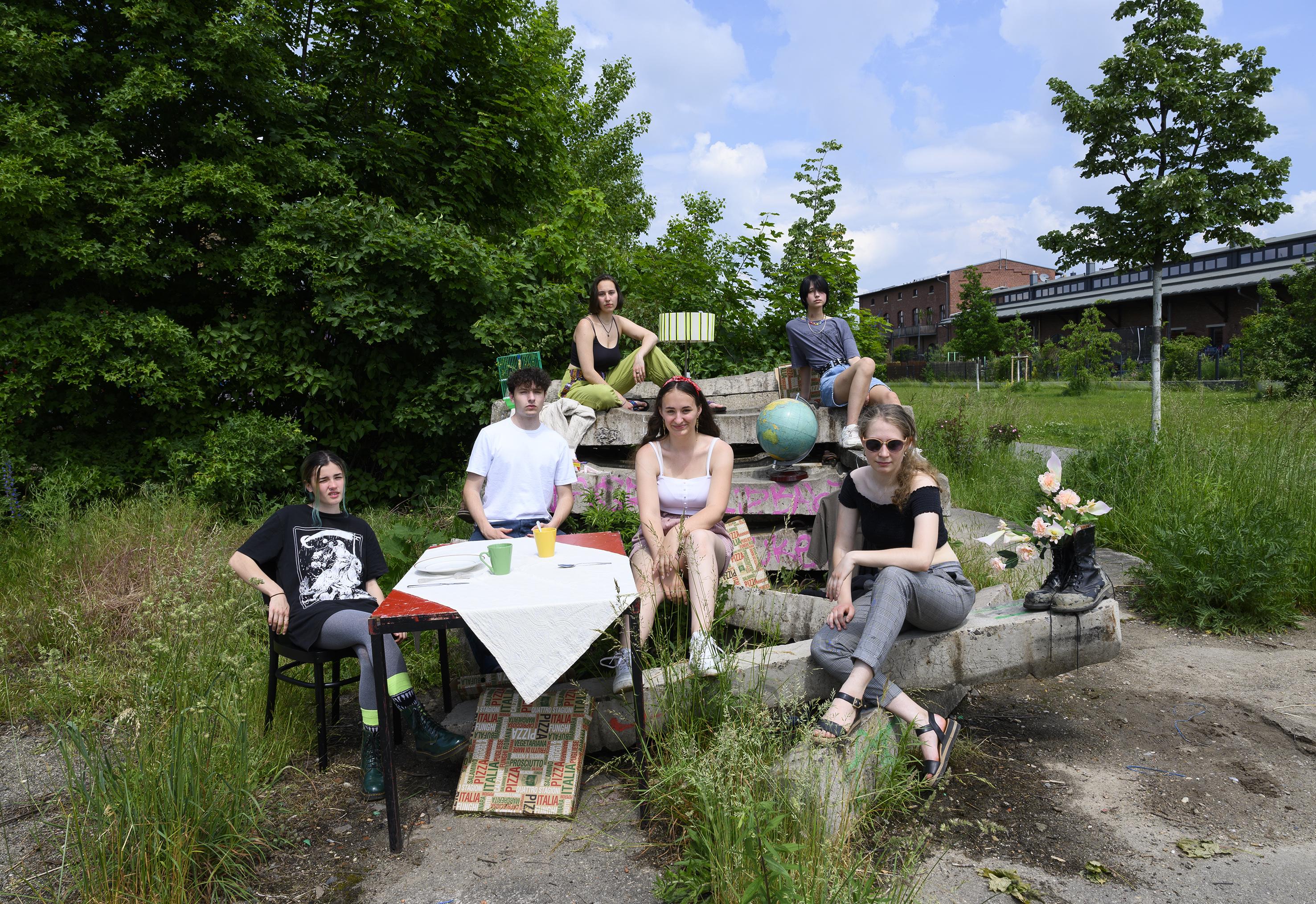 6 Jugendliche auf Betonklötzen im Grünen mit alltäglichen Gegenständen installiert.