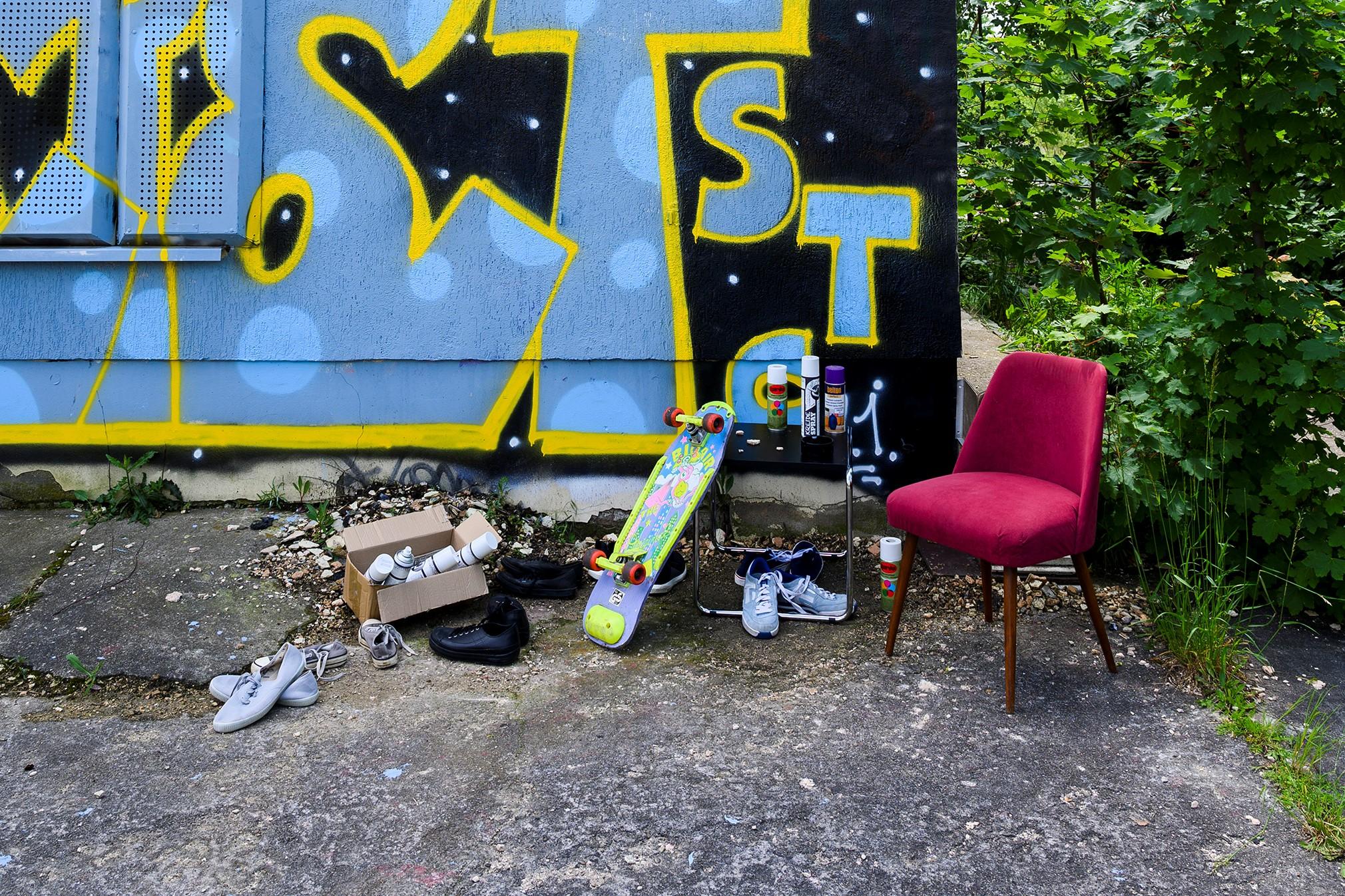 Roter Stuhl, Skateboard, diverse Schuhe und Spraydosen vor blau-gelb besprühter Hauswand.