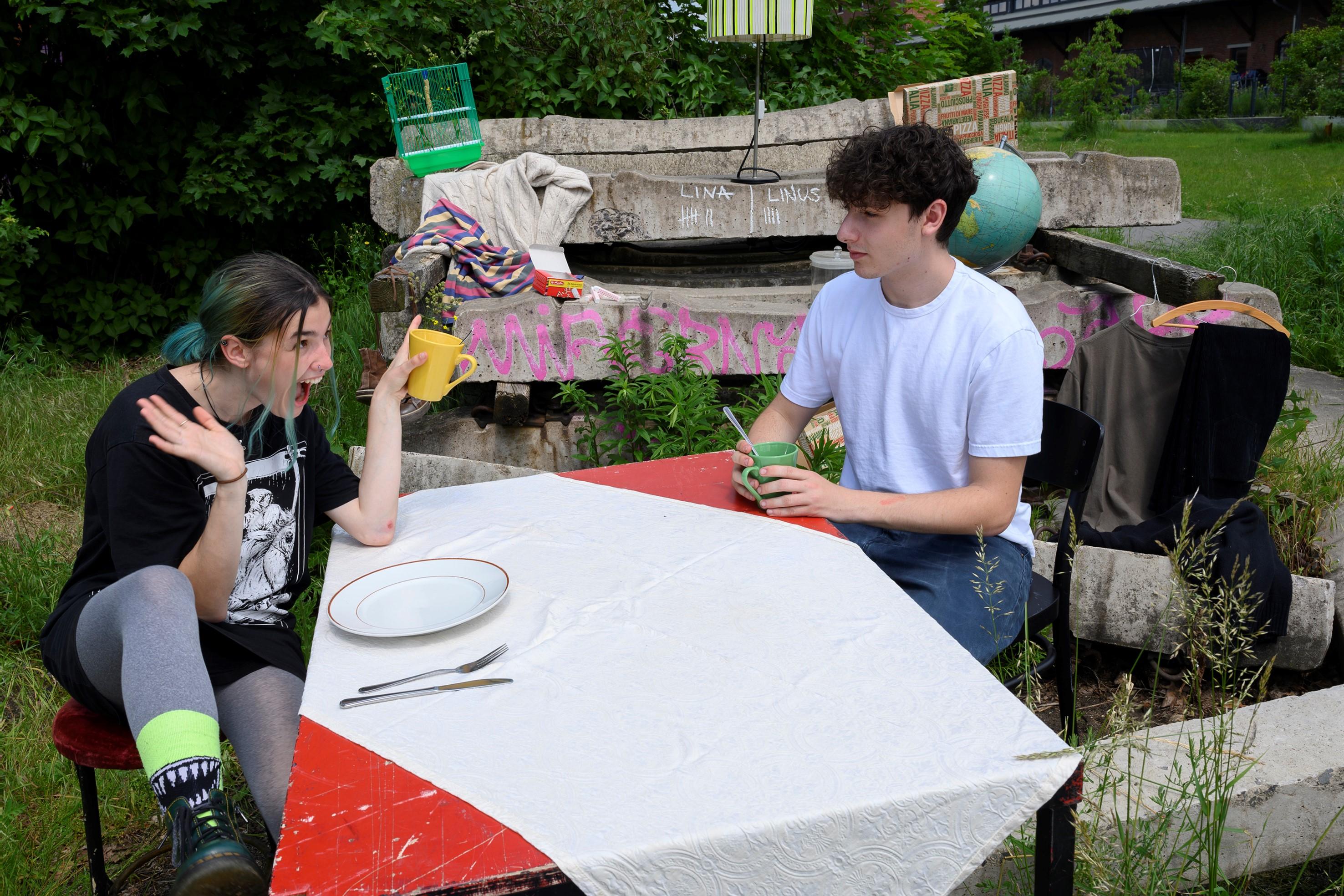 Eine erfreute und eine nachdenkliche Personen gegenüber sitzend an einem Tisch mit Geschirr vor Betonelementen im Gras.