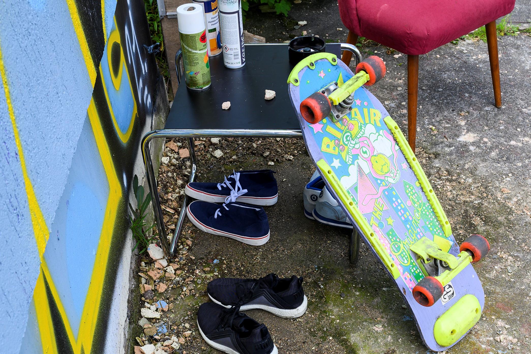 Neonfarbiges Skateboard lehnt an Beistelltisch vor besprühter Hauswand.