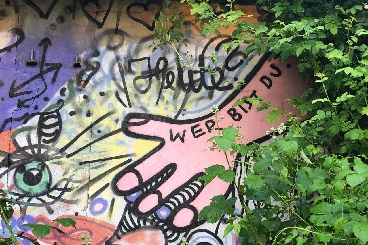 """Eine mit Graffiti besprühte Wand mit Büschen im rechten Bildrand. Auf der Wand eine große gesprühte Hand. Über der Hand die Frage """"Heute?"""". Auf der Hand die Frage """"Wer bist du?"""""""