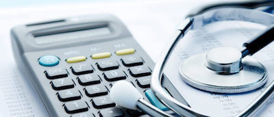 Image of a Stethoscope and calculator on a desk