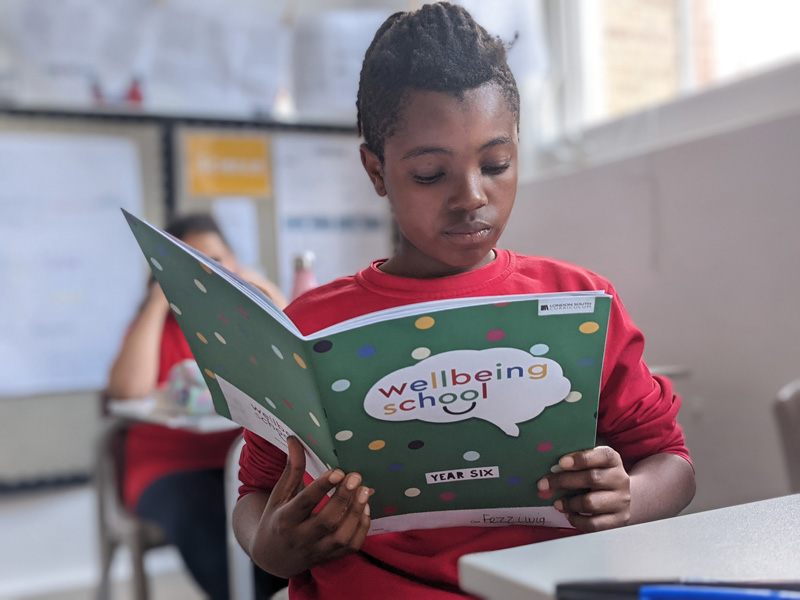 Boy reading a booklet from the Wellbeing School