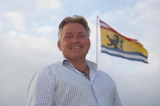 Foto van Jos de Wilde met de vlag van provincie Zeeland op de achtergrond, image