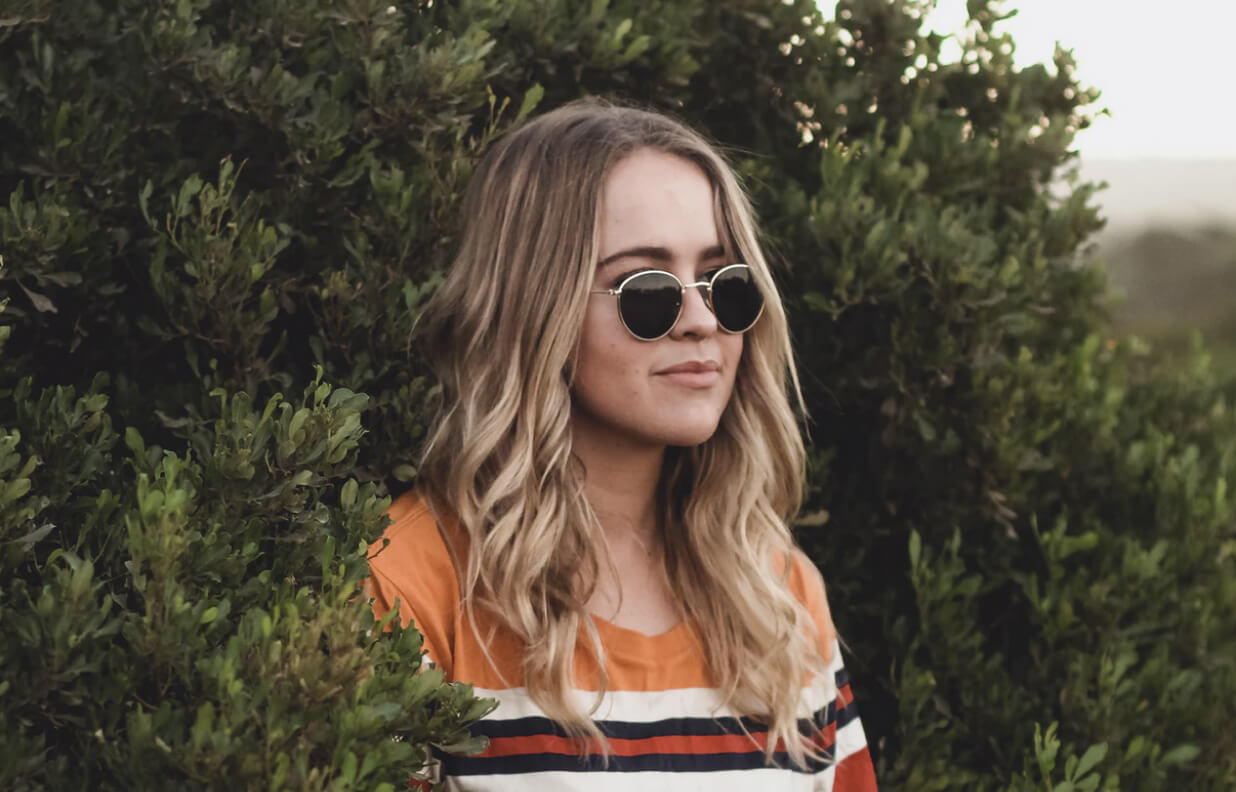 A woman with blonde hair and sunglasses looks off into the distance and is surrounded by tall bushes