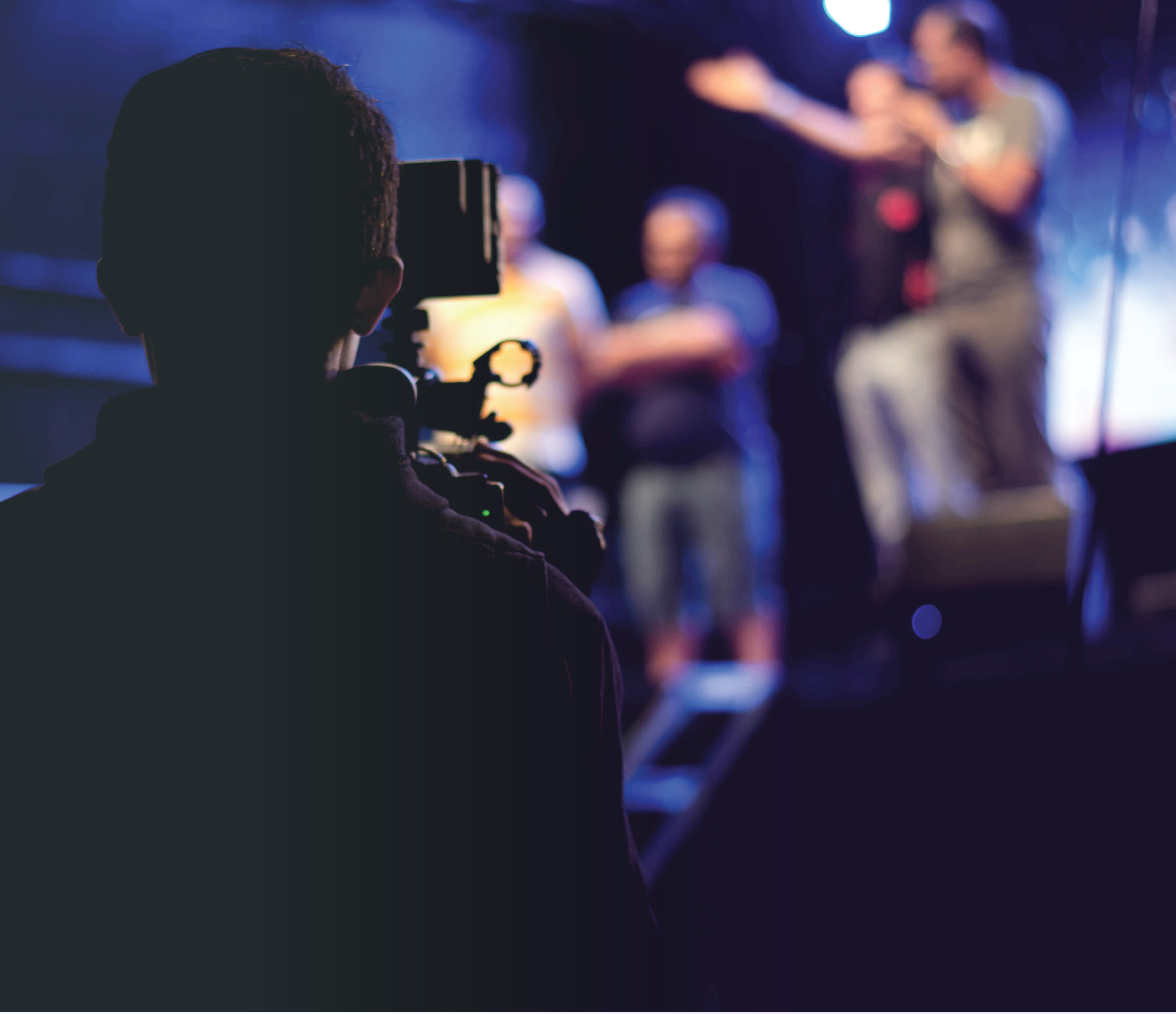 one cameraman filming a group of four enthusiastic speakers on a stage in front of him