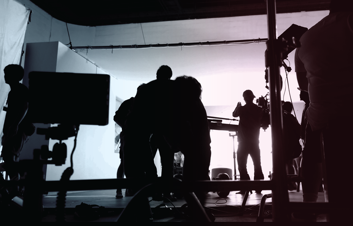 a backlit film crew with multiple cameras, screens, and wires flims something on a white background set
