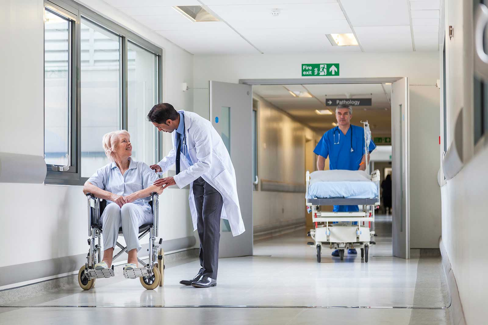 doctor talking to woman in a wheelchair in a hospital ward