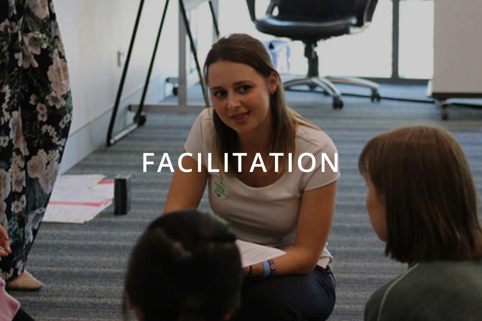 Ashleigh kneeling speaking to someone with facilitation overlay