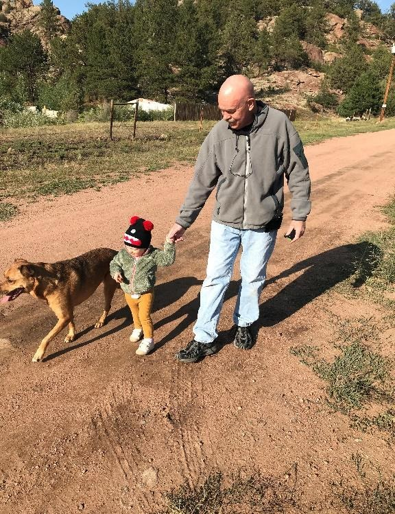 A person and a child walking a dog on a dirt roadDescription automatically generated with low confidence