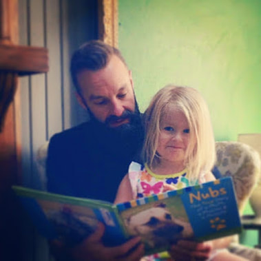 A father reading a story to his daughter