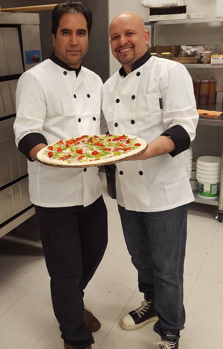 Joe holding a pizza