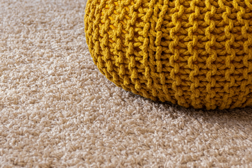 Carpet next to a knitted ball.