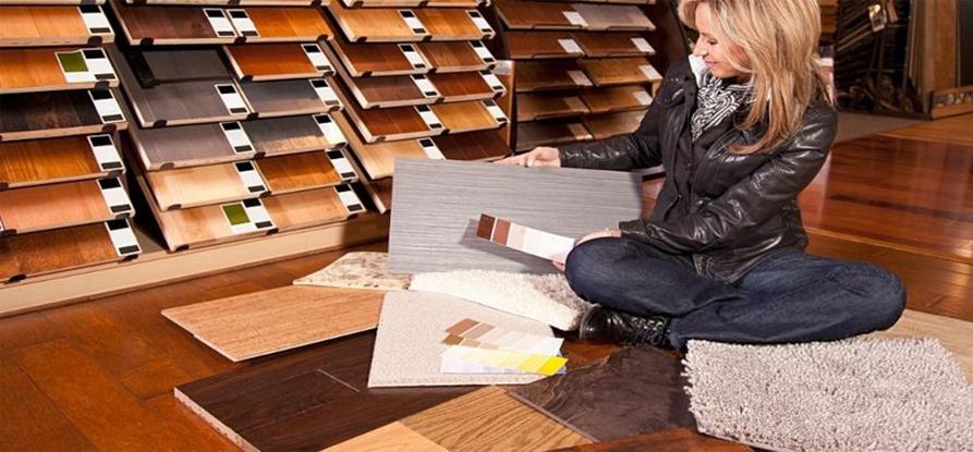 A woman looking at flooring.