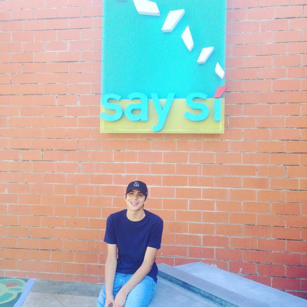 Jonathan Rodriguez/ Rodzjon/ Jon Rodz in front of the SAY Si signage
