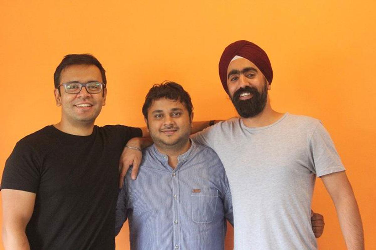 Akshay, CEO, Maddy, CTO and Jaideep, CMOO against an orange backdrop
