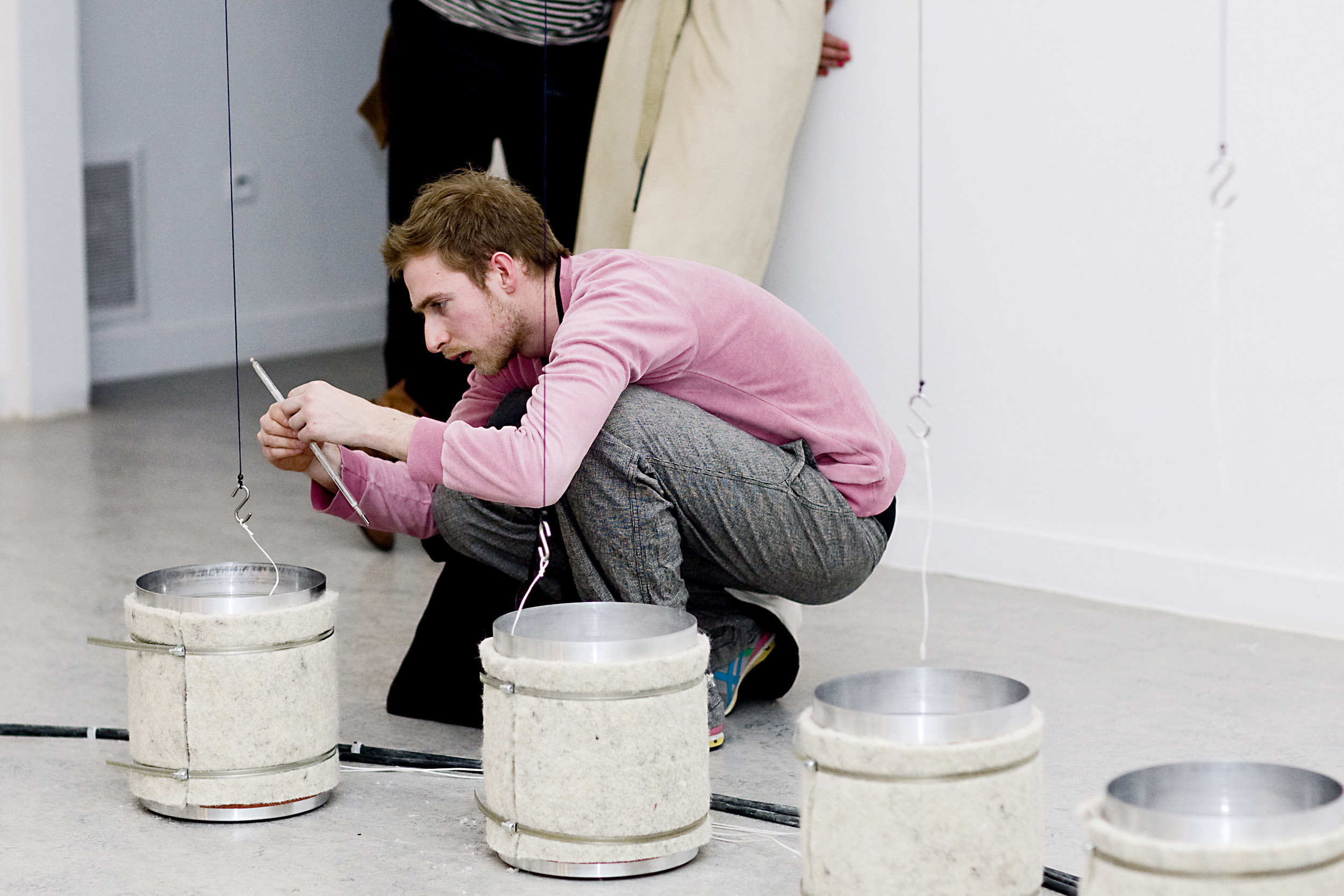 Tim fixing candle wick to the end of the dipping lines at Z33 gallery