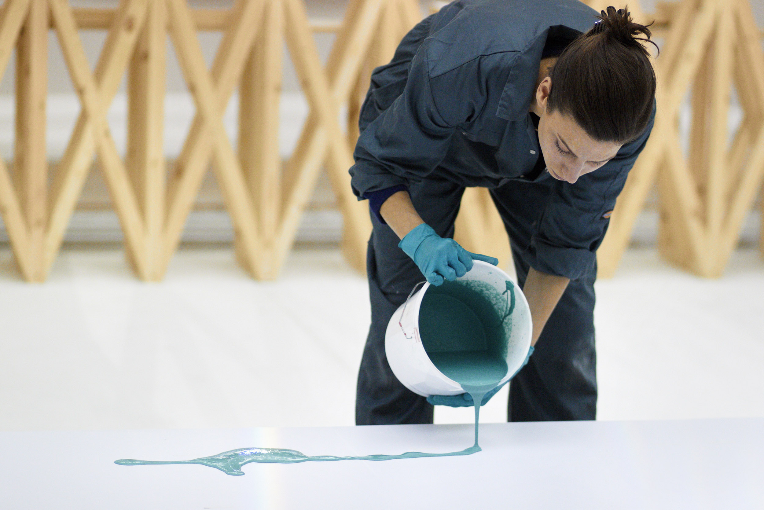 Sarah pouring a bucket of green poly-concrete with timber bar structure behind