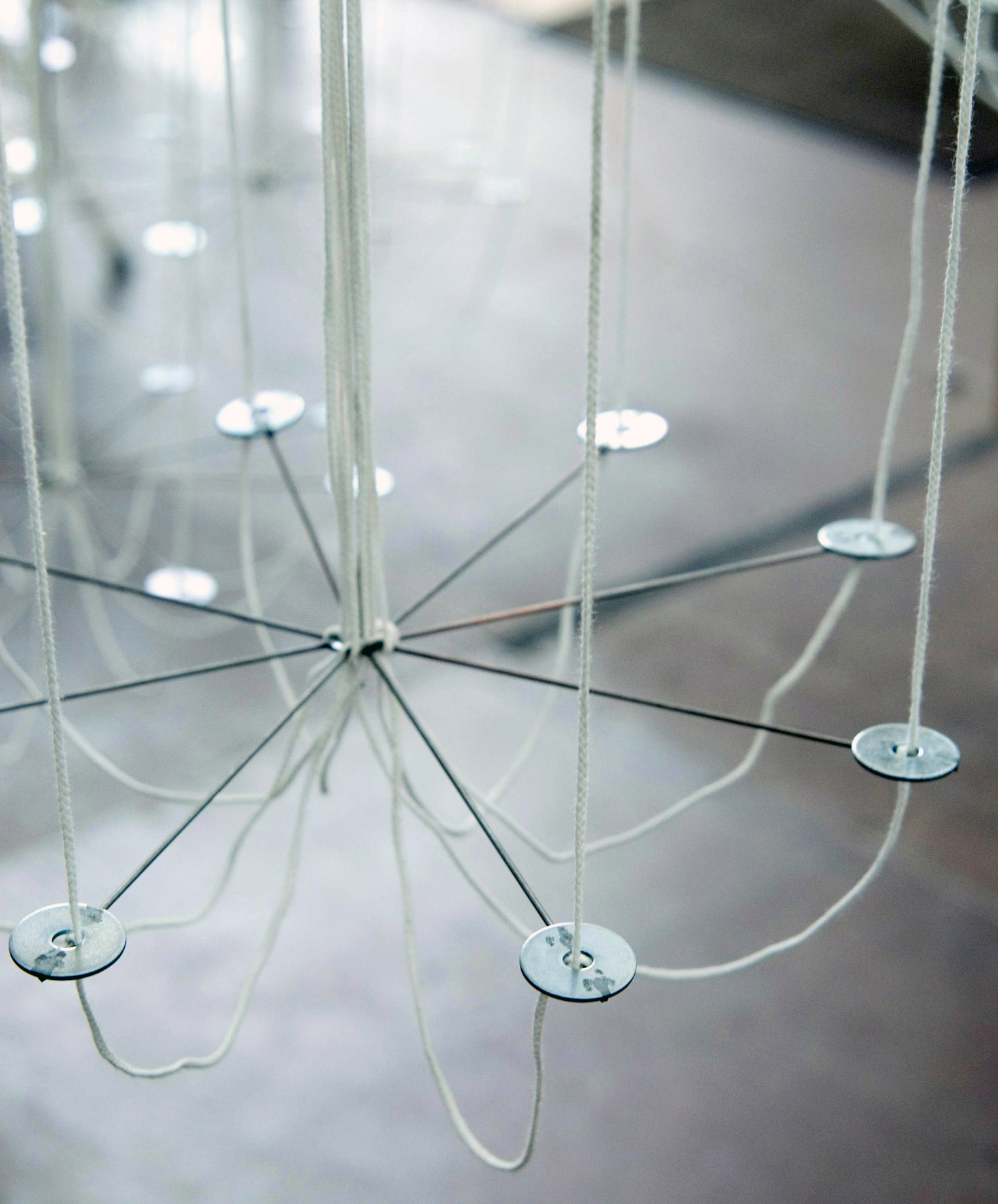 A detail of the way the wick is strung through the wire chandelier frame