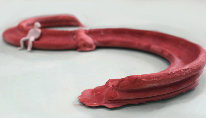 A concept model for Running Mould showing plasticine figure reclining on oversize red plaster bench