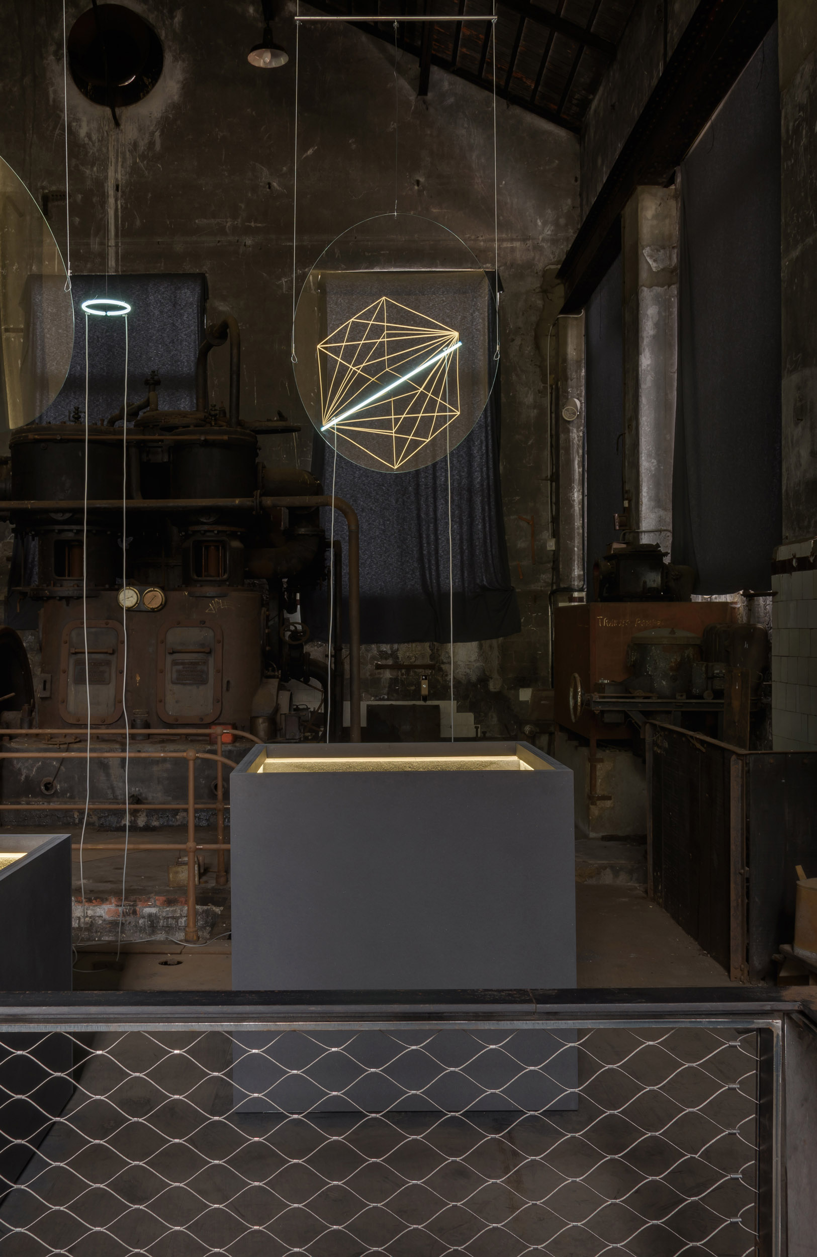 A cubic wireframe Luminary sculpture appears as a reflection around a strip of neon
