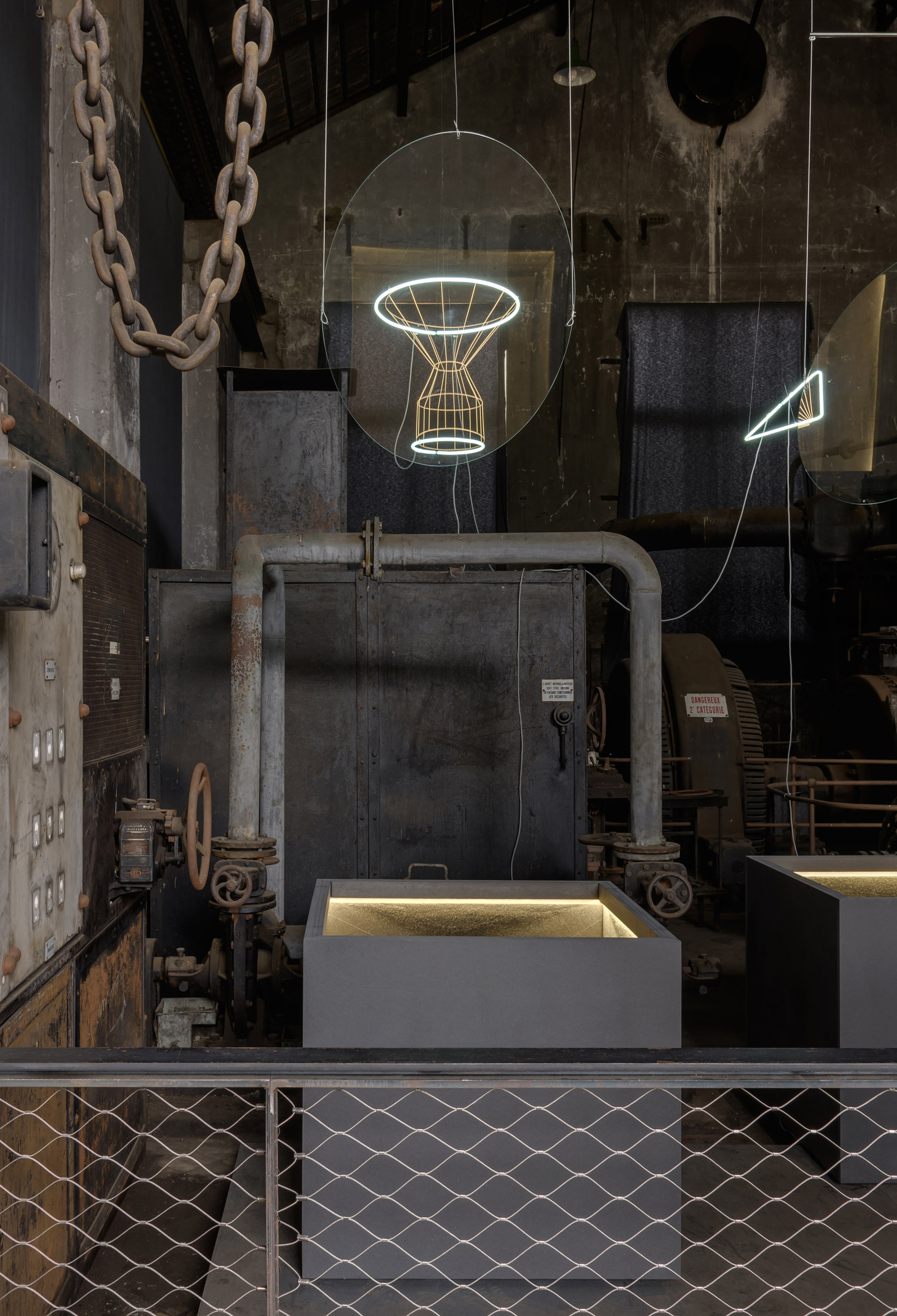 A chimney shaped wireframe sculpture appears as a reflection around two neon rings