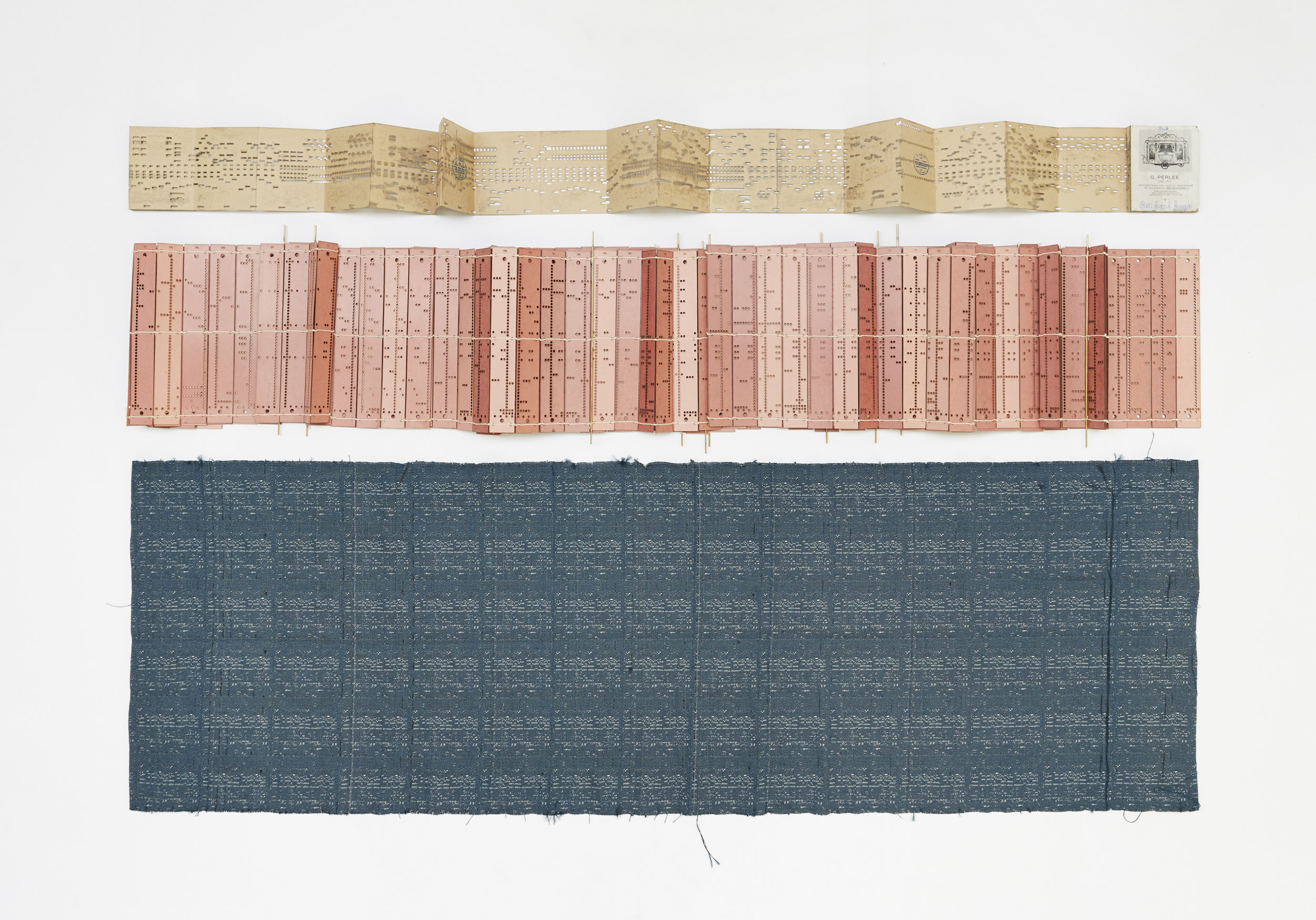 A studio photo that shows an original organ book, a weaving book and the fabric which was the outcome of the project