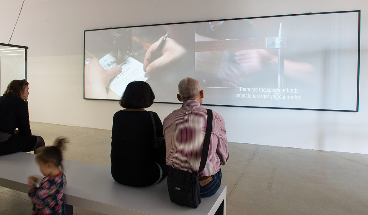 Visitors sat on a bench watch the Woven Song film installation