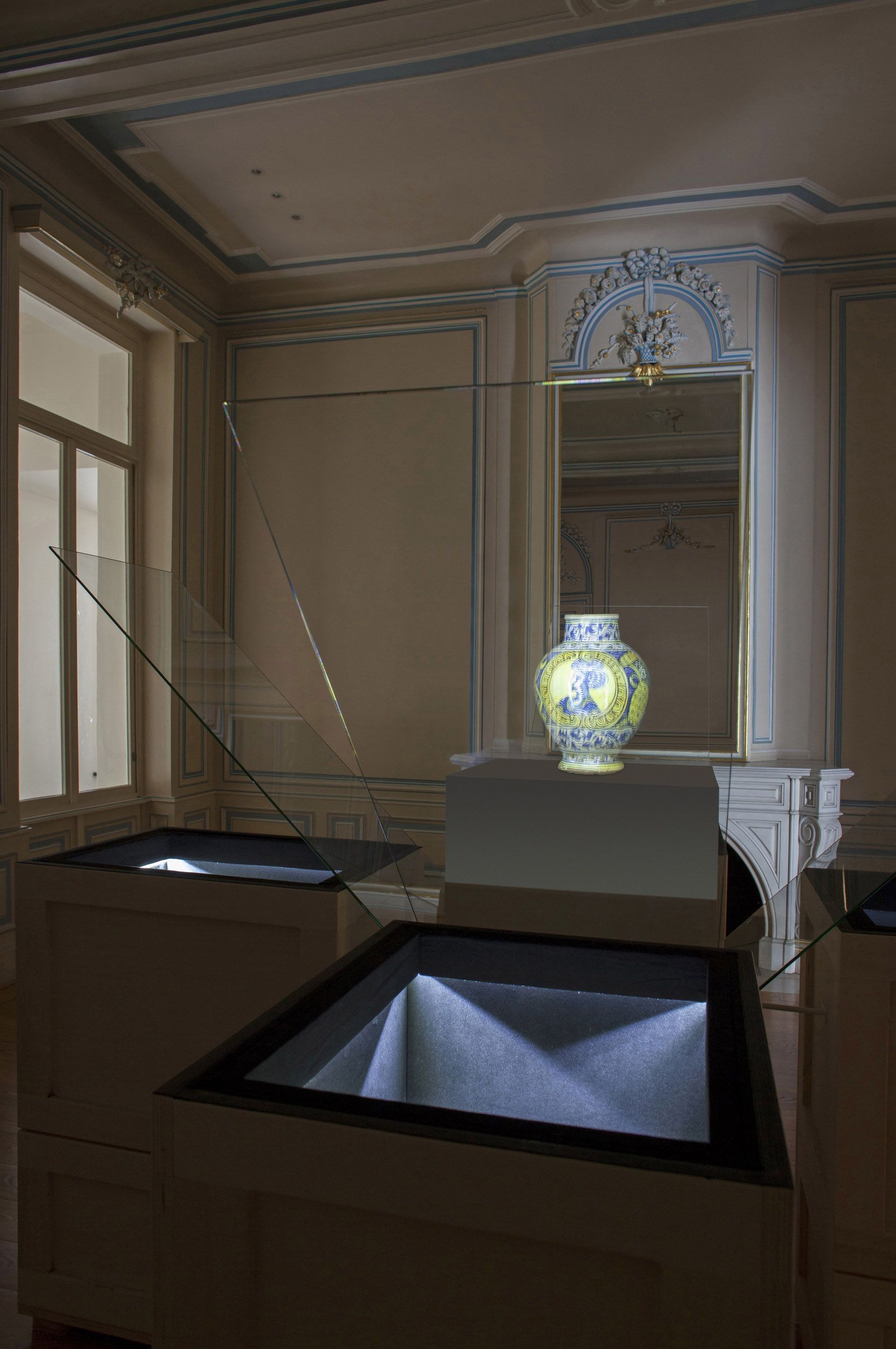A reflected vase appears on a plinth