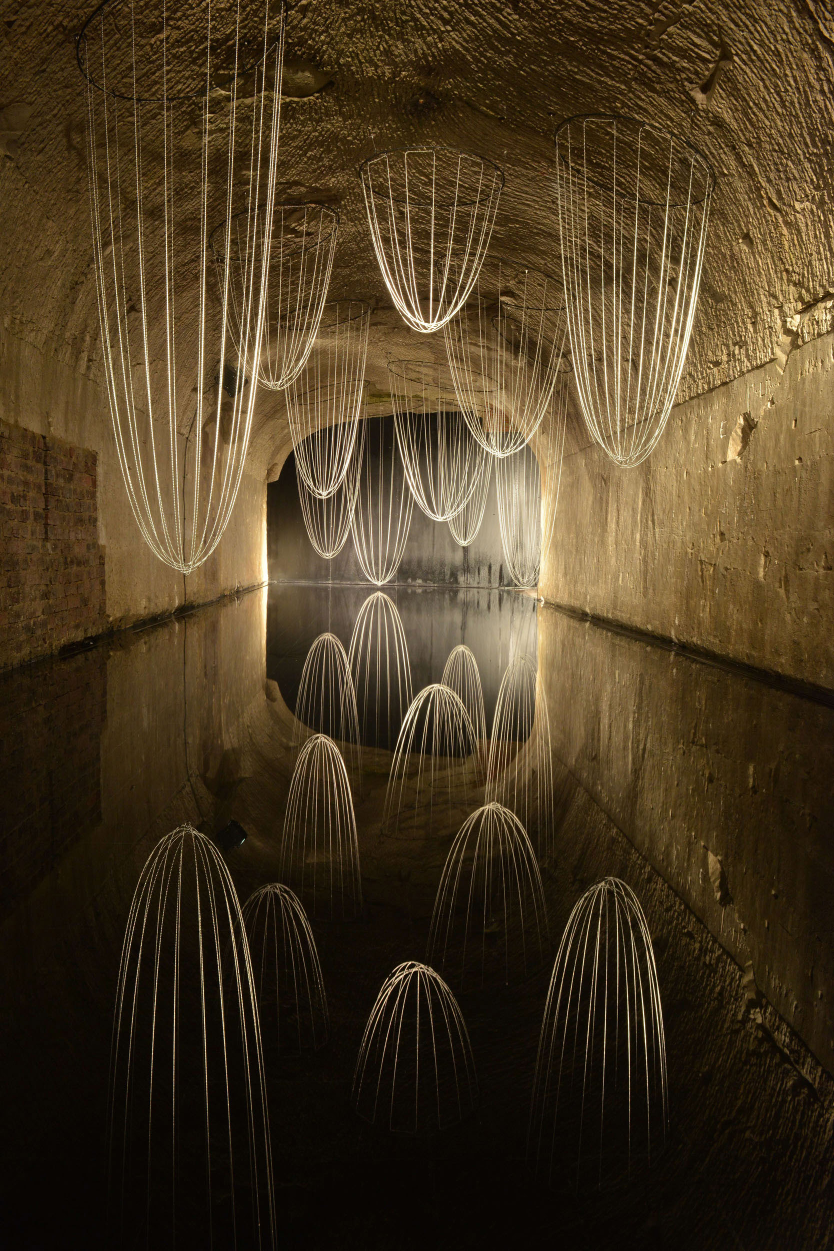 Lost Time is an installation of strung beads that are reflected over a shallow body of still water. The weight of the suspended beads creates natural drapes that, when reflected in the surface of the water, appear as a landscape of towering structures.