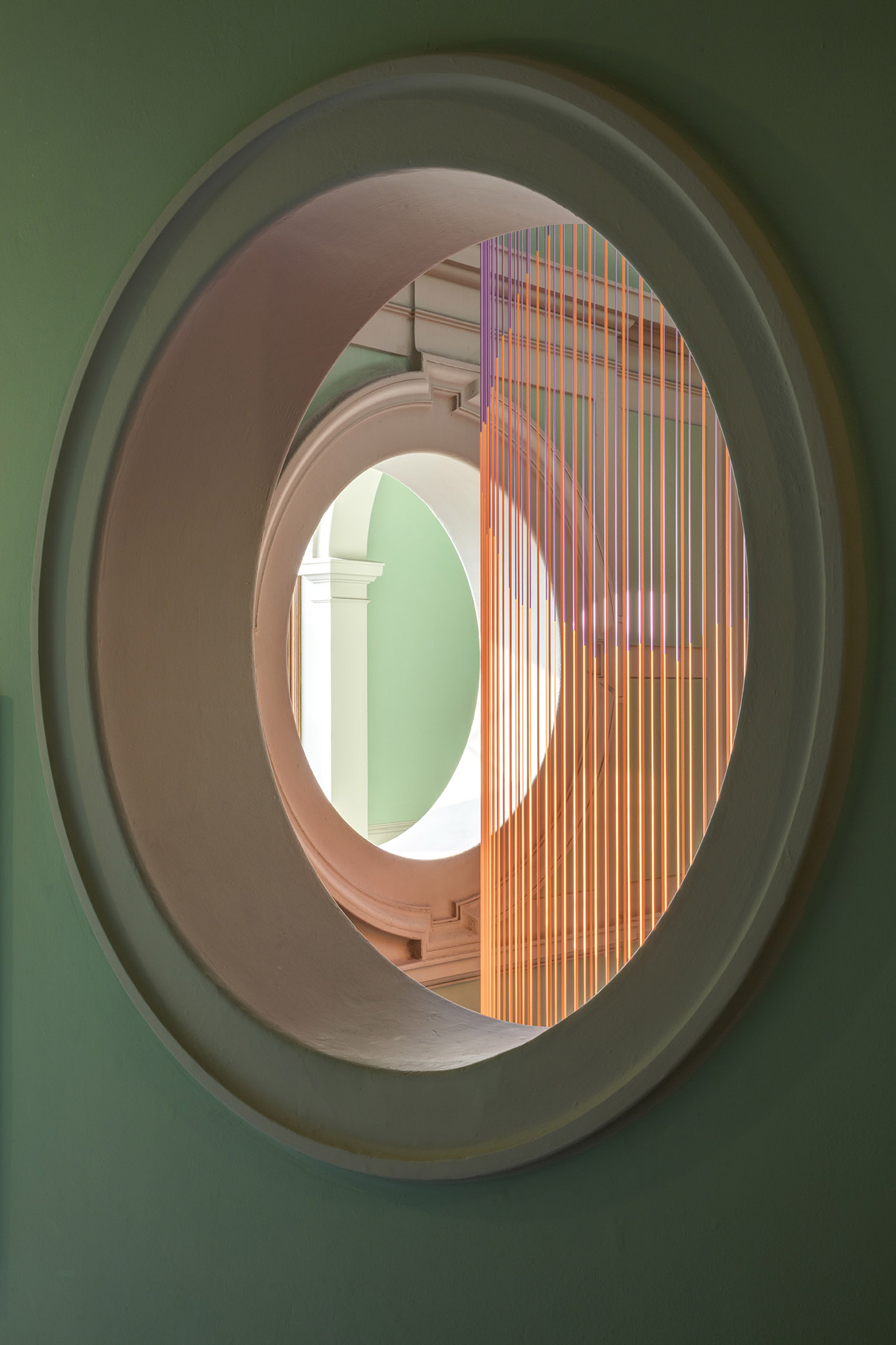 View of Green Room silicon cords through porthole on stairwell