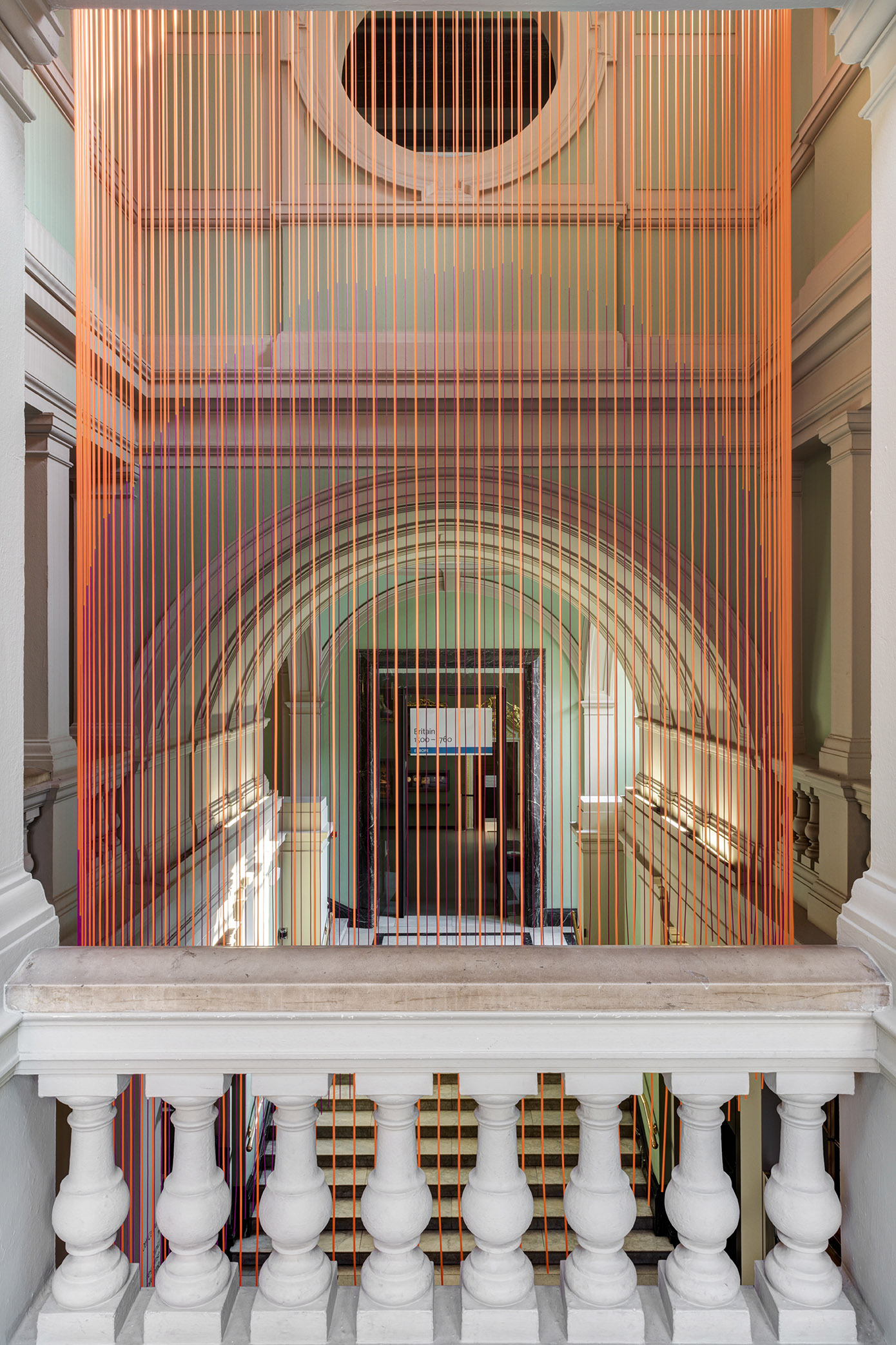 Orange silicon cords dangle in Victoria and Albert Museum entrance above visitors heads