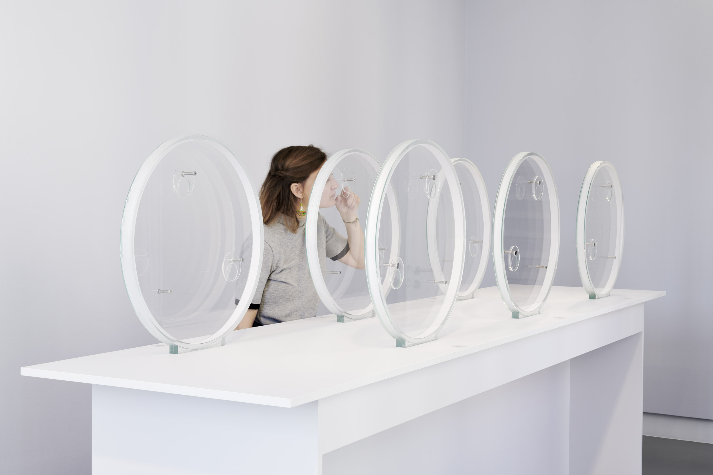 A visitor smells perfumes within round glass vessels