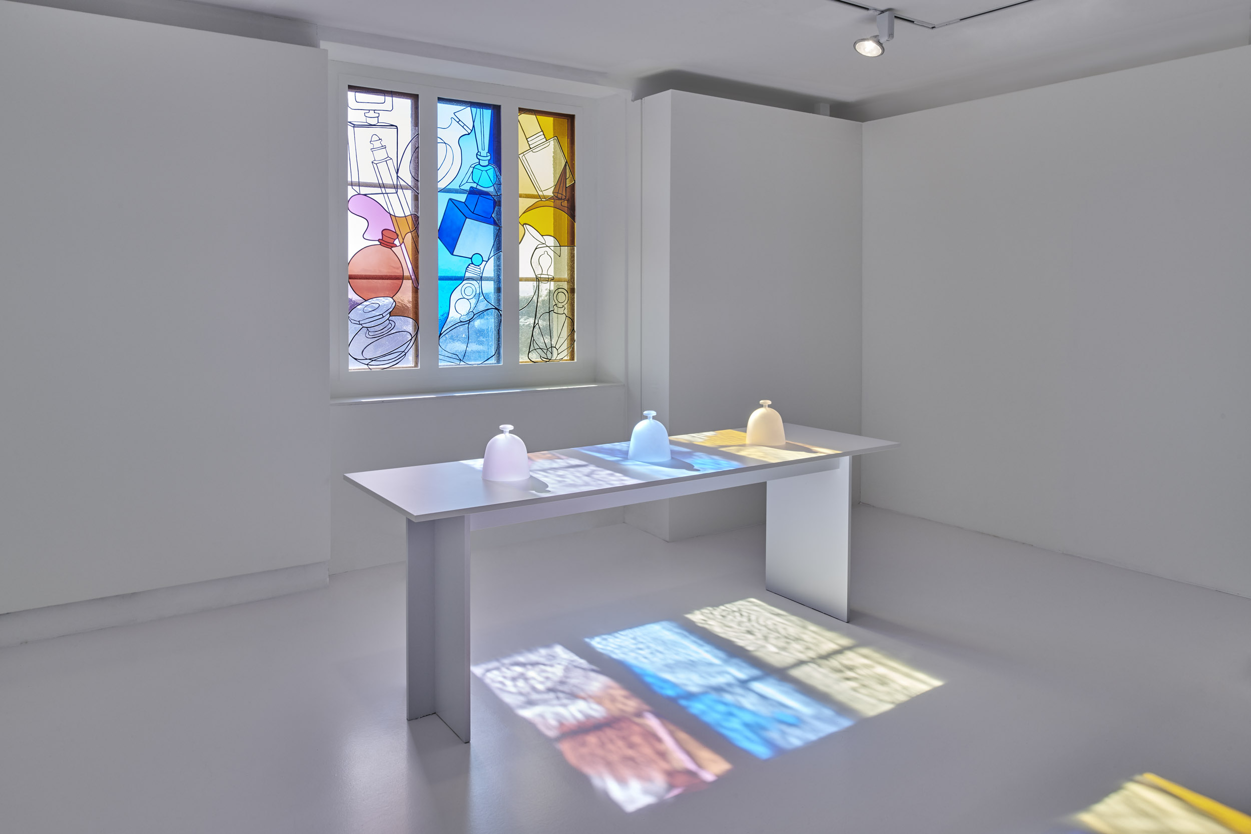A stained glass window depicting perfume bottles casts coloured light upon perfumes presented on a table