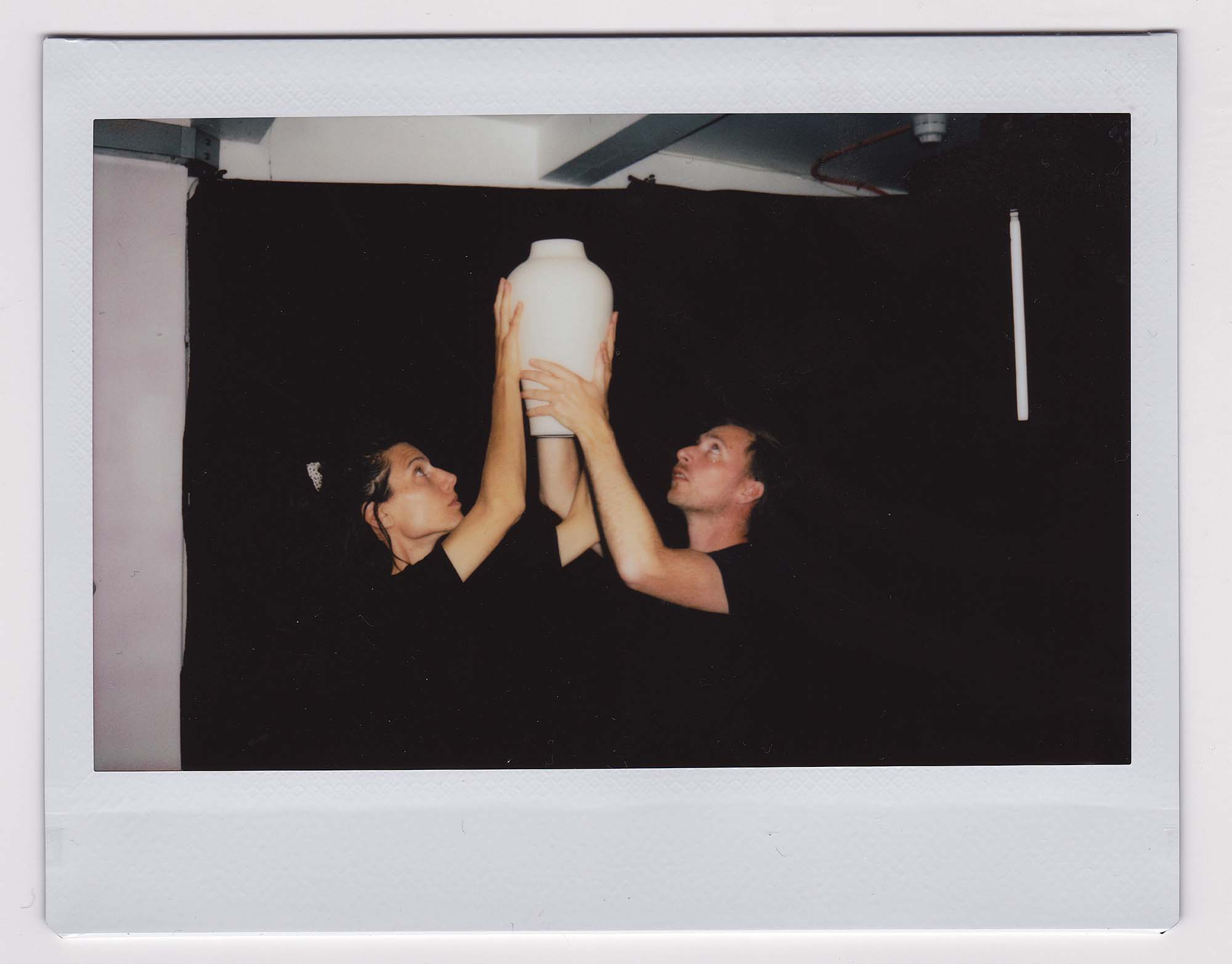A portrait of Tim and Sarah raising a Hold Me vase above their heads