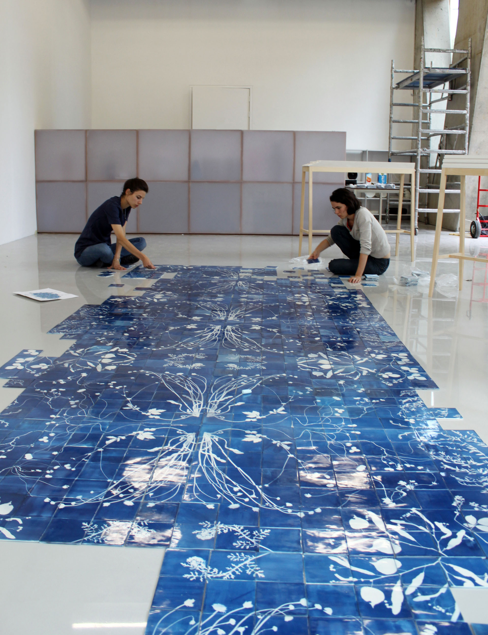 Laying out a large Blueware tile mural on the floor