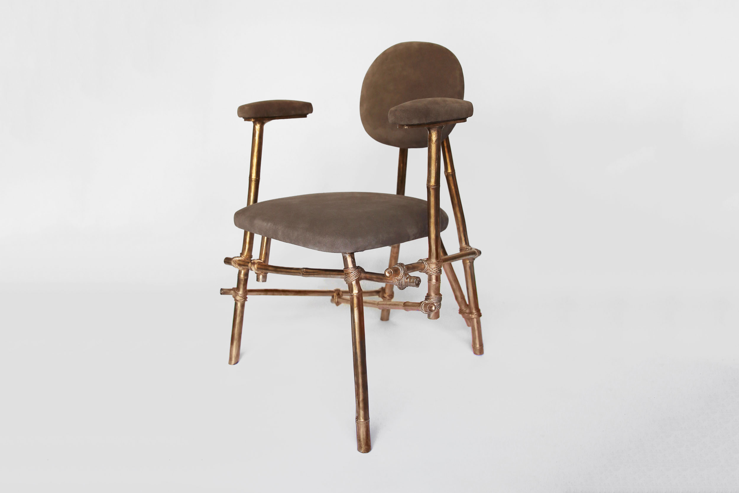 A front view of a Les French chair with bronze cast bamboo frame and leather upholstered seat and rests