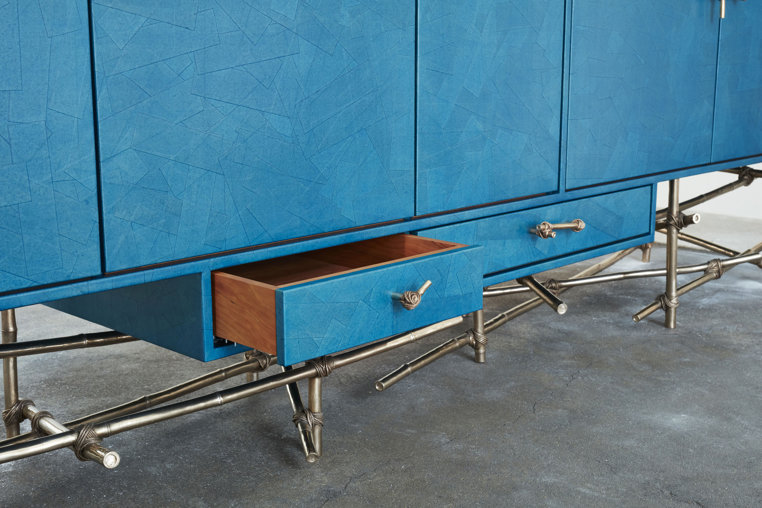 A drawer detail of large sideboard showing turquoise gum paper finish