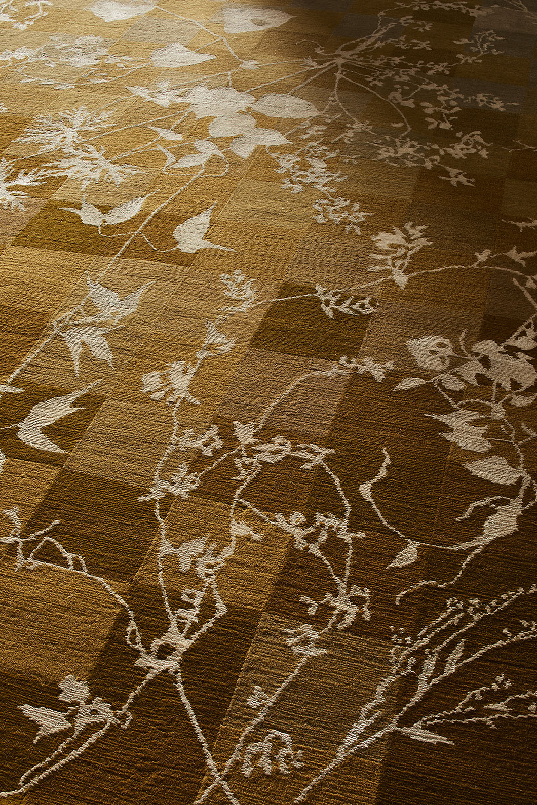 Detail of a copper colour Botanical Rug in shadow