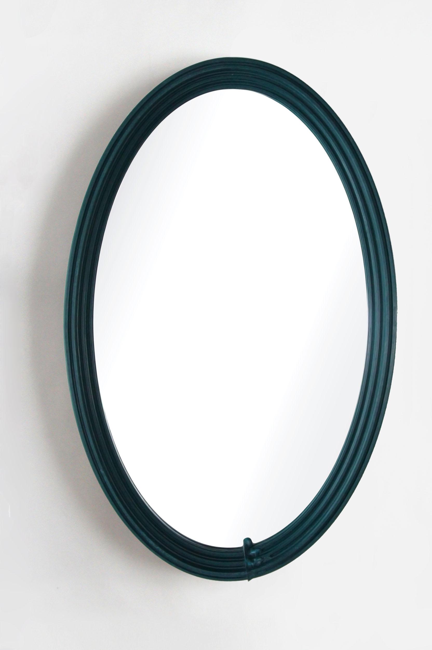 An elliptical Bench Mould mirror in dark blue