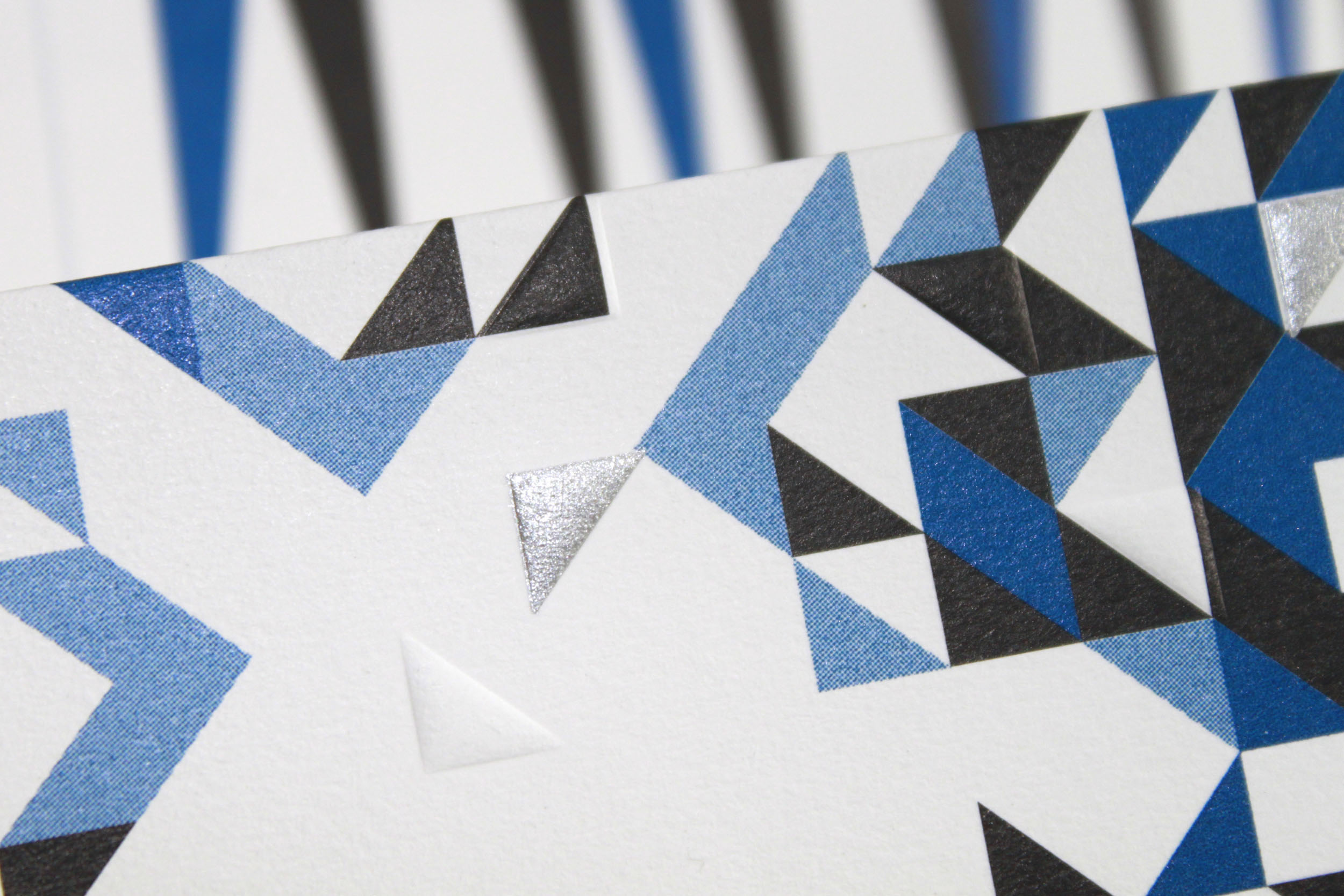 A detail of a Paper Plane showing embossed letter press design of triangles