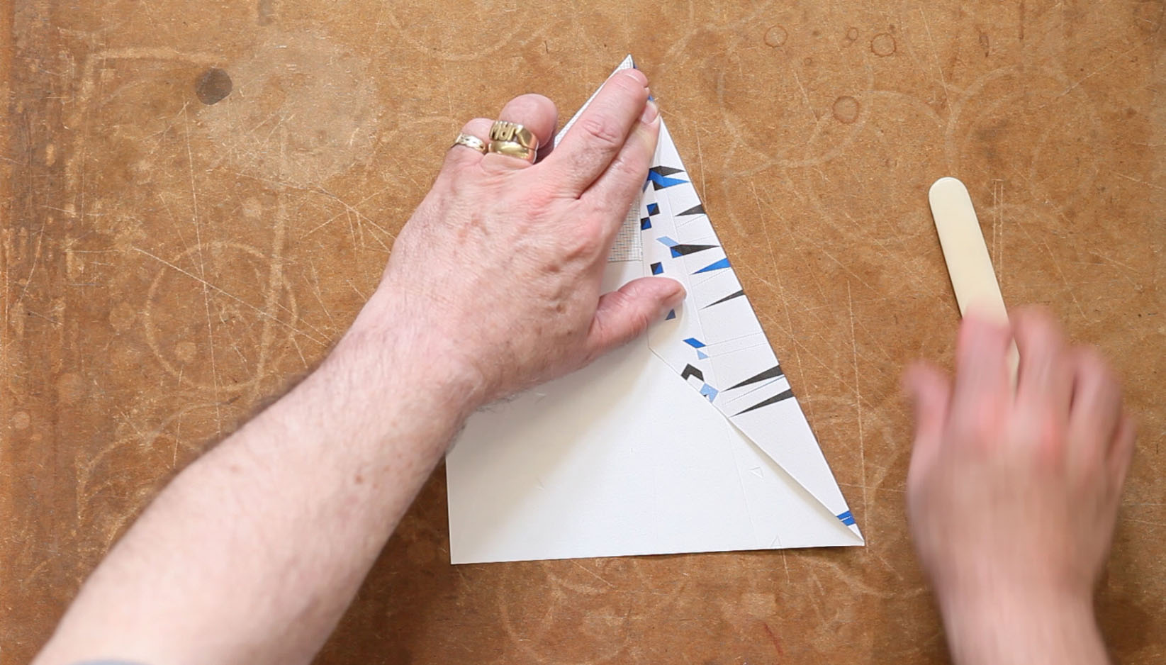 A film still showing a Paper Plane being folded by hand