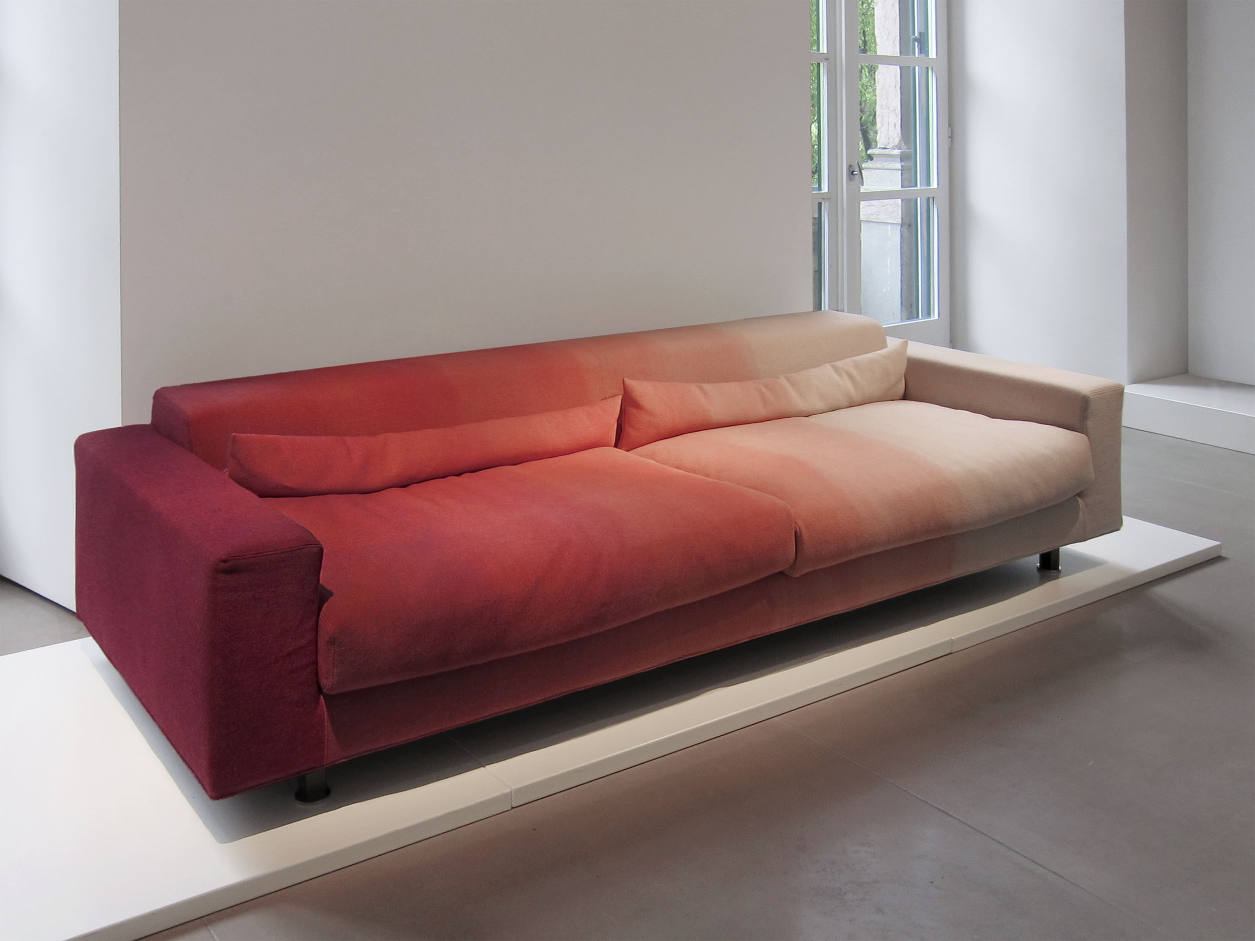 A sofa that has been upholstered with dip dyed fabric from intense to red to natural wool