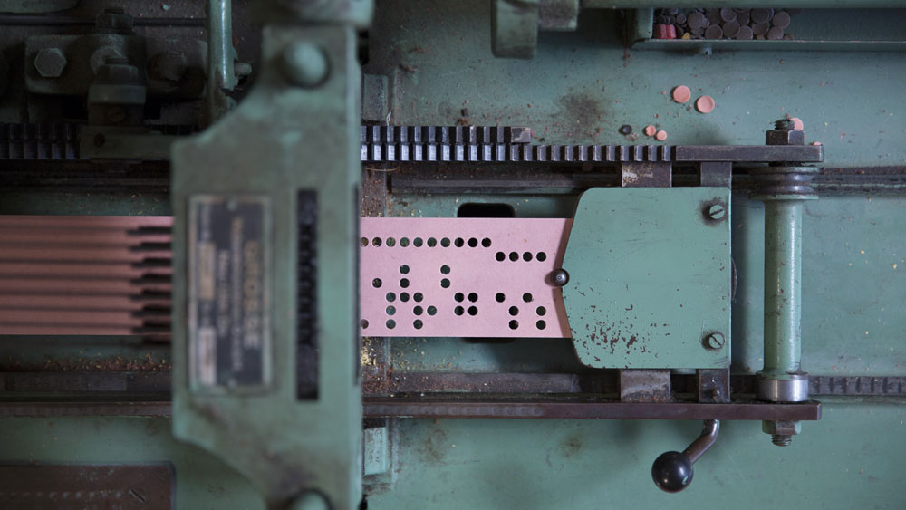 A machine that punches holes in Jacquard weaving cards