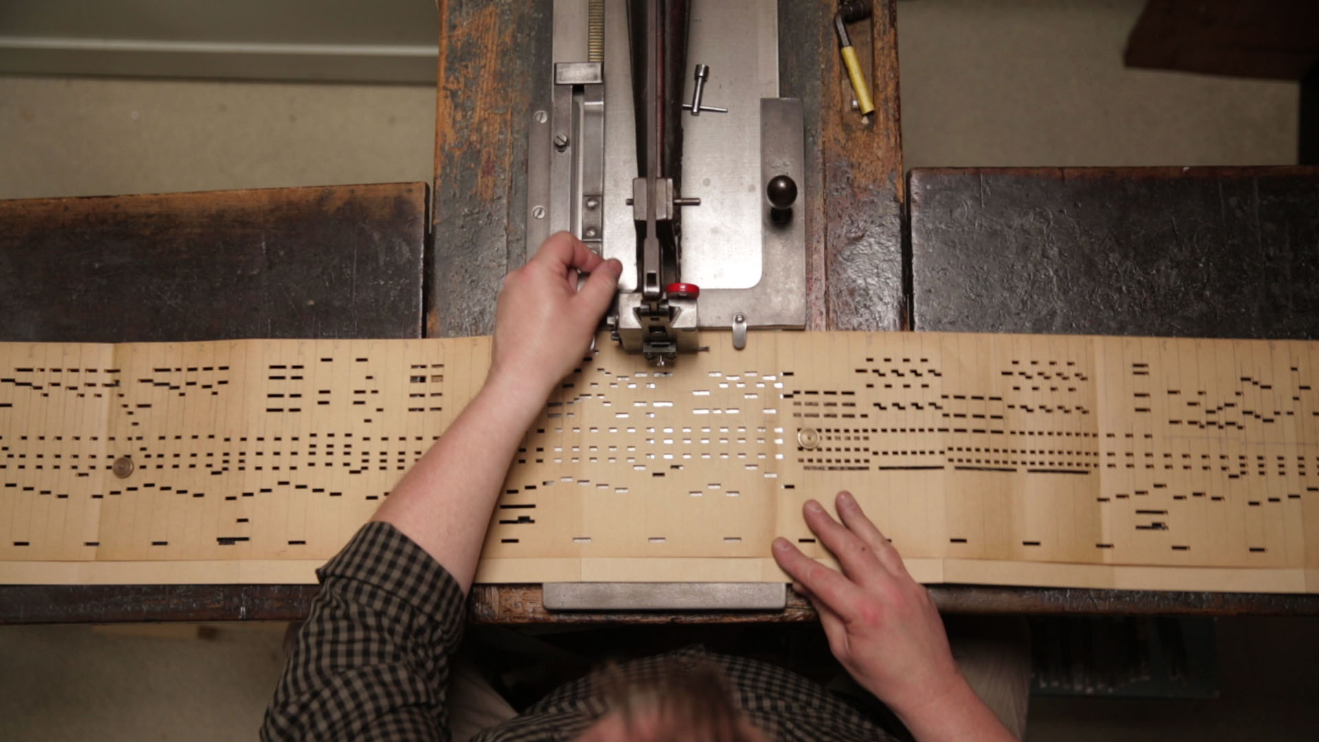 A top view of the making of an organ book using a punching machine