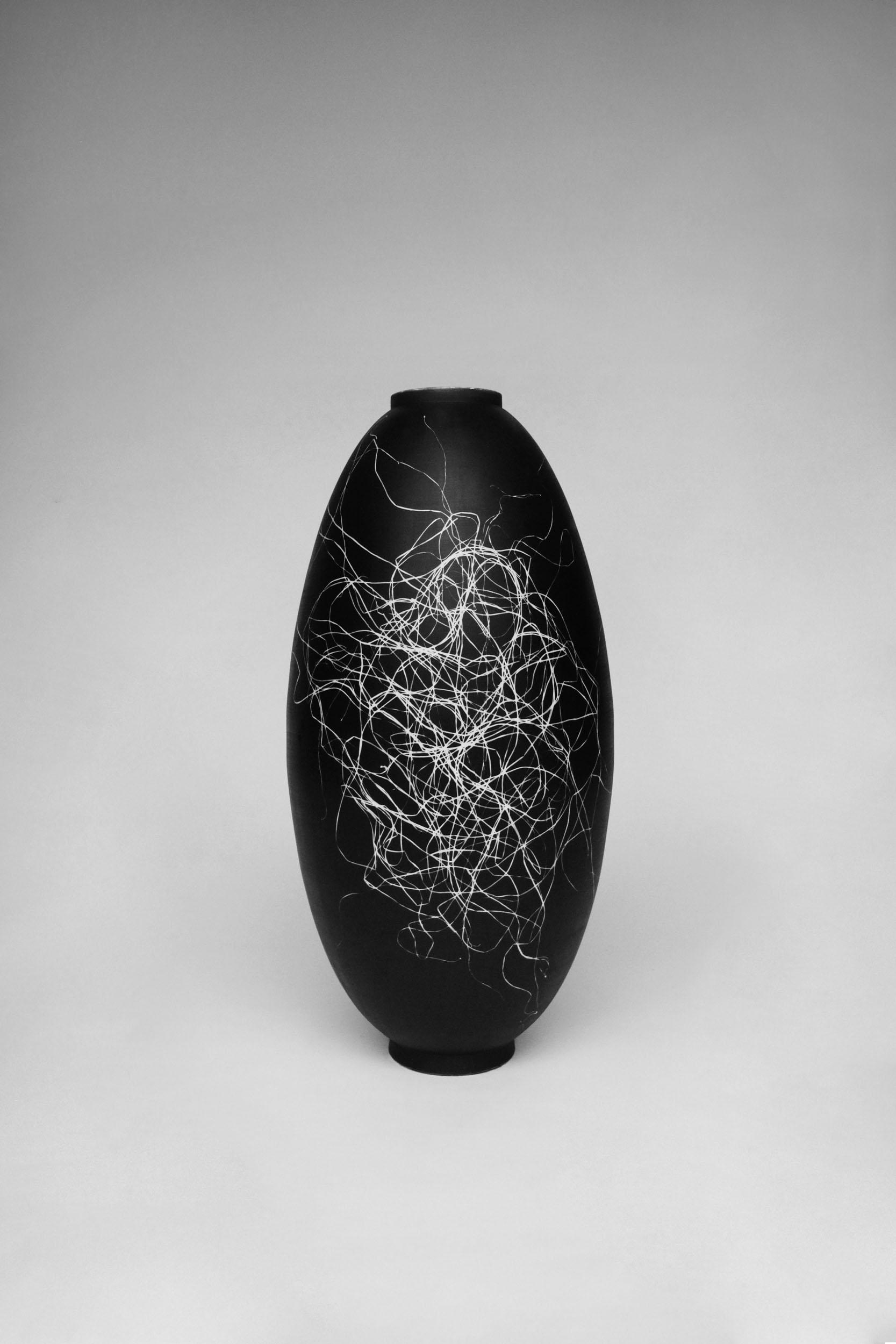 A tall Silverware vase with silver gelatin sea spaghetti photogram