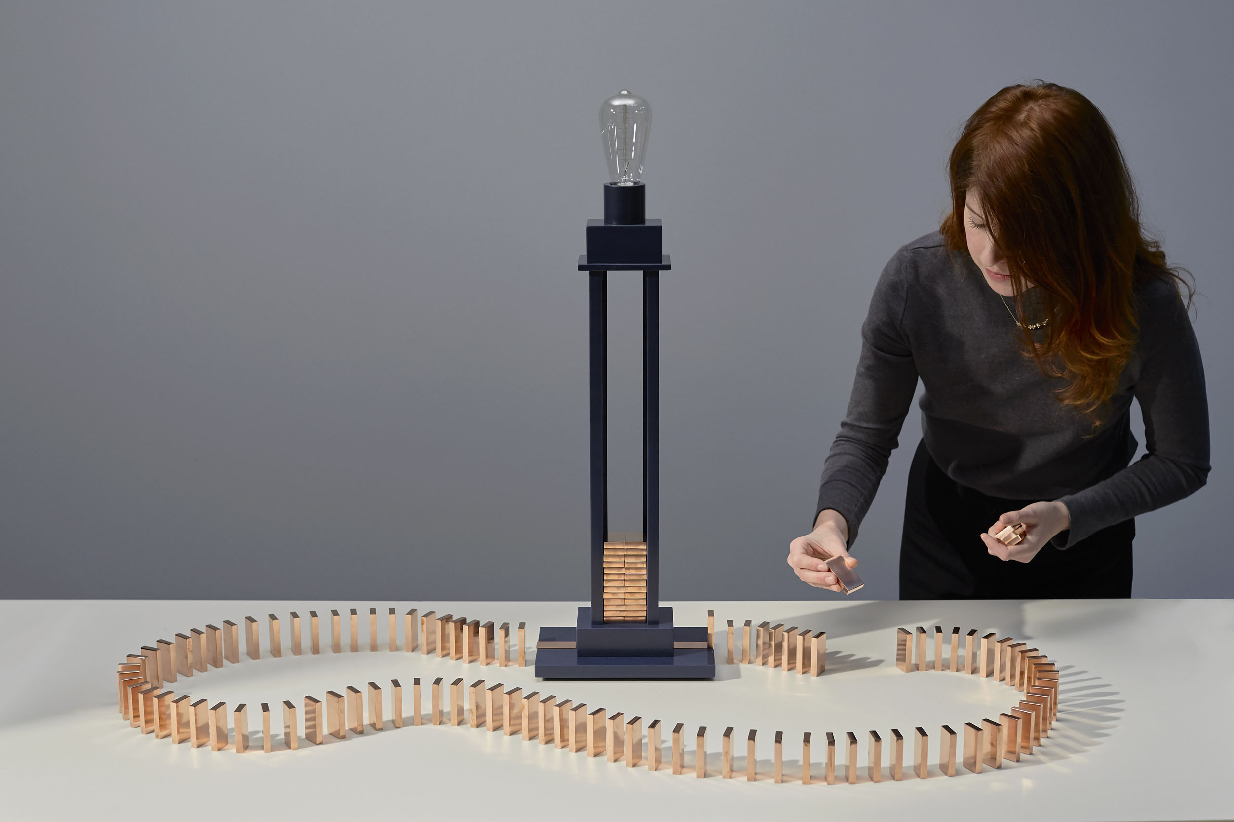 A girl starts the domino rally which switches the Domino Light on