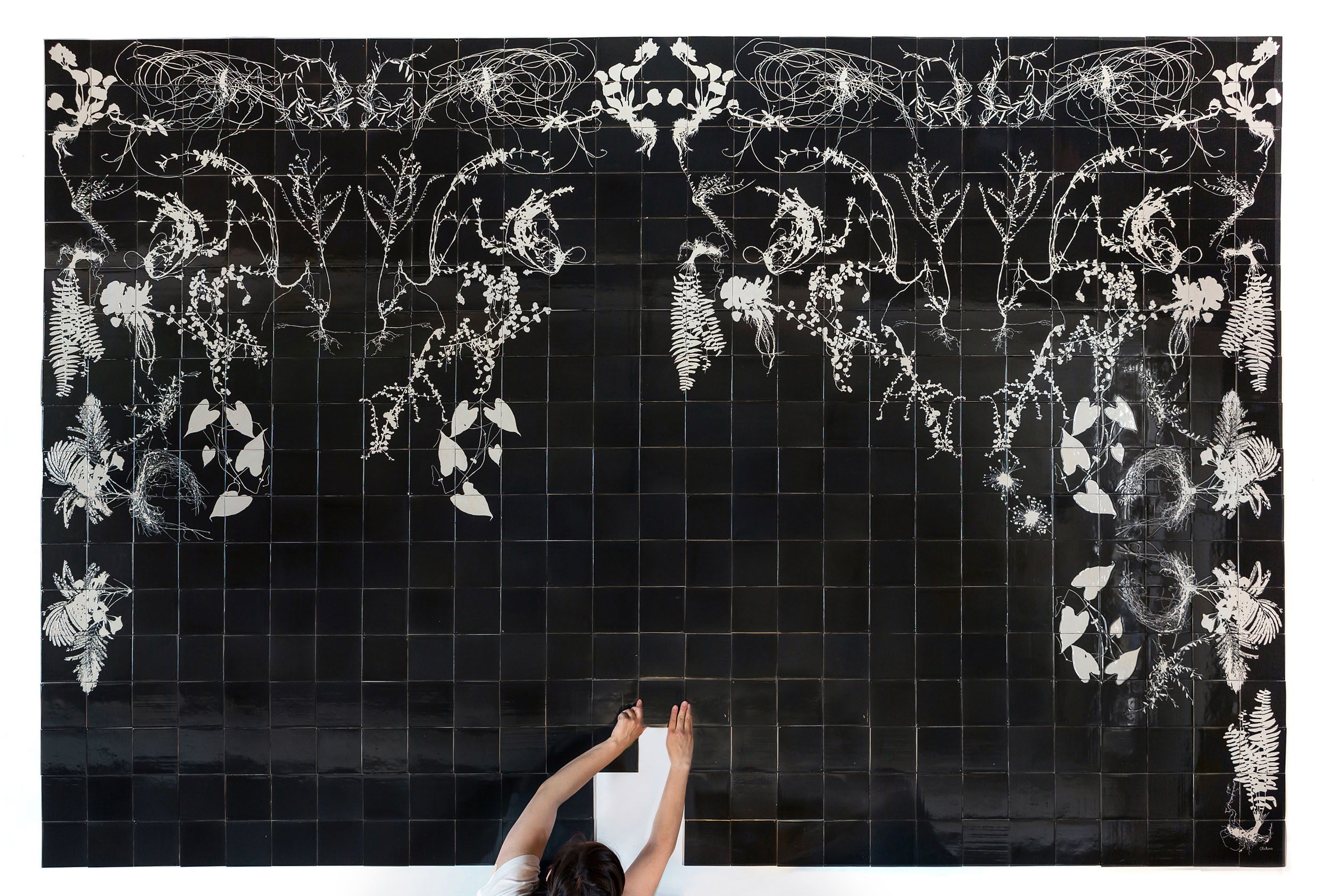 A Botanical Tiles Mural layed out on the floor in black and white glaze