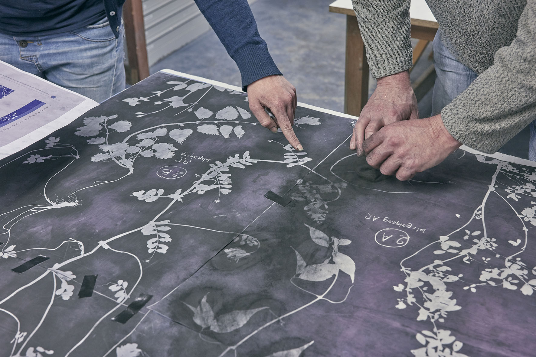 A layout design for Botanical Tiles with hands pointing